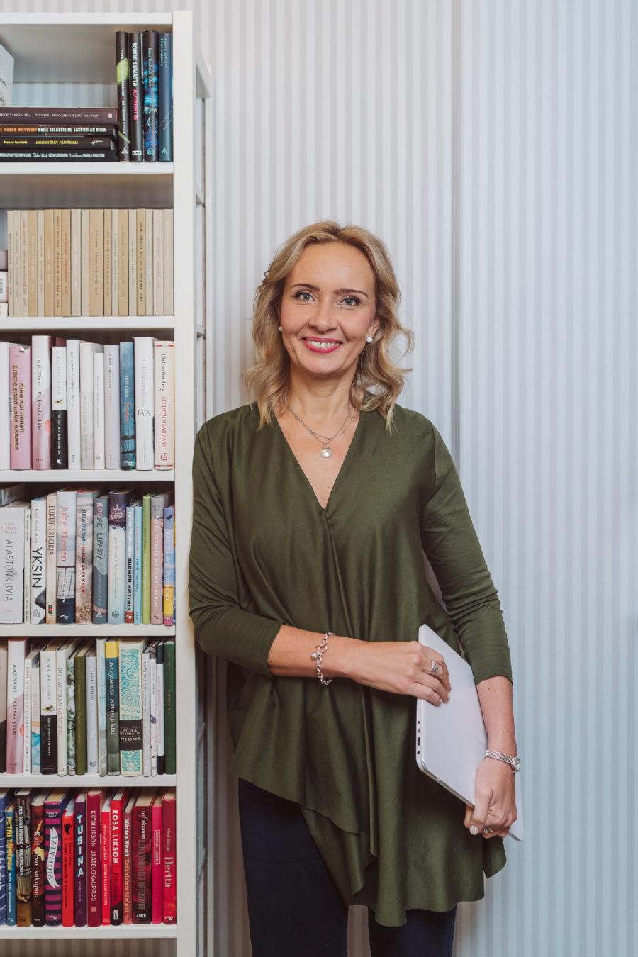 Kuvassa toiminnanjohtaja Ilmi Villacís nojaa kirjahyllyyn